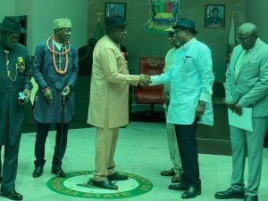 Diri in warm handshake with Wabote while others looked on